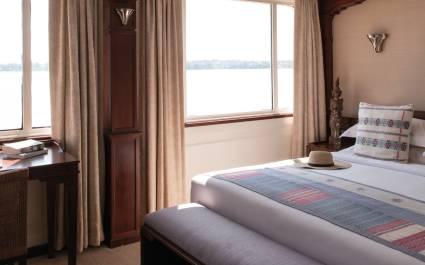 Bett und Fenster mit Blick aufs Wasser auf dem Schiff 'Road to Mandalay', Indien
