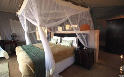 Kuscheliges Bett mit Moskitonetz in einem Lodge-Zelt