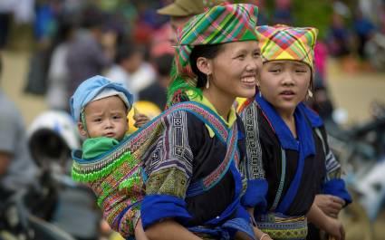 Frau in traditioneller Tracht trägt Kleinkind