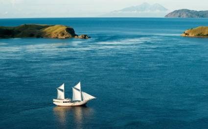 Luftaufnahme von weißem Segelboot der Alexa Cruises vor felsiger Uferlandschaft in Indonesien