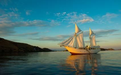 Außenansicht von weißem Segelboot der Alexa Cruises vor felsiger Uferlandschaft in Indonesien