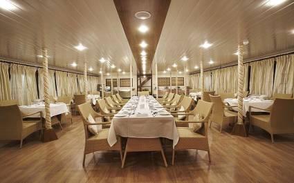 Langer gedeckter Tisch im weiß-beige eingerichteten Schiffsrestaurant der MV. Mahabaahu in Assam, Indien