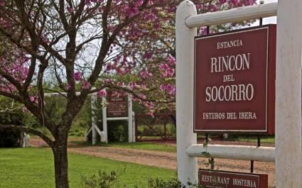 Rotes Eingangsschild der 'Estancia Rincón del Socorro' mit blühendem Baum in Esteros del Iberá in Argentinien