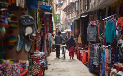Menschen gehen durch die vollgepackten Stände des Marktes in Kathmandu, Nepal
