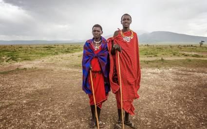 Portraitfoto von zwei traditionell gekleideten Männern der Massai vor der weiten Landschaft des Ngorongoro-Reservats in Tansania, Afrika