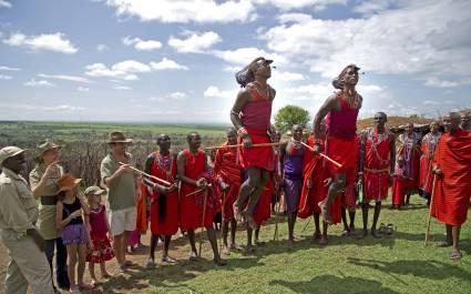 Bewohner eines Maasai-Dorfes in traditionellen Kleidern mit einem Gast von Enchanting Travels
