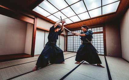 Zwei Männer in traditioneller japanischer Kleidung trainieren den Samurai-Kampf