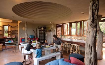 Mann spielt am Tisch mit kleinen Kindern in der Madikwe Safari Lodge