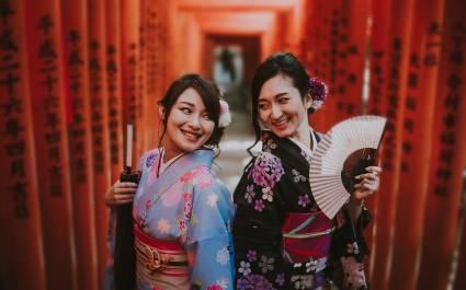 Zwei Japanerinnen in Kimonos lächeln sich zu