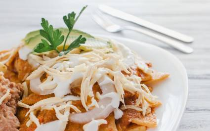 Chilaquiles - Lightly fried tortillas pieces served with scrambled or fried eggs, pulled chicken and topped with refried beans, salsa, cheese, and sour cream