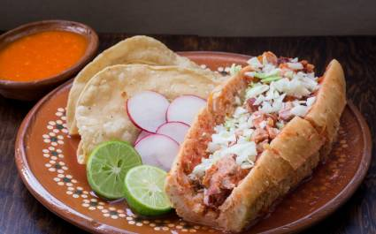 Tortas - A bun stuffed with meat and vegetables and topped with shredded cabbage, cheese, and sour cream.