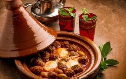Fleischbällchen in geöffneter Tajine, dem traditionellen marokkanischen Schmorgefäß aus Lehm