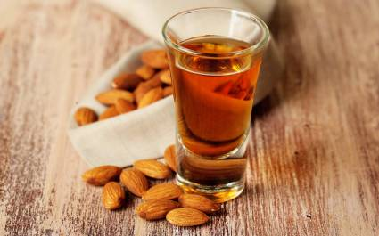 Enchanting Travels Italy Tours Dessert liqueur Amaretto with almond nuts, on wooden table