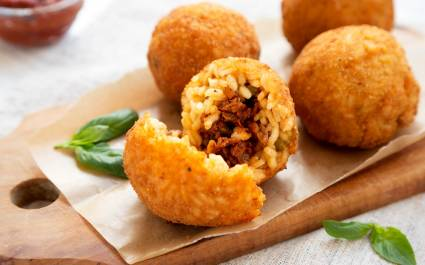 Enchanting Travels Italy Tours Homemade fried Arancini with basil and Marinara on a white wooden background, side view. Italian rice balls