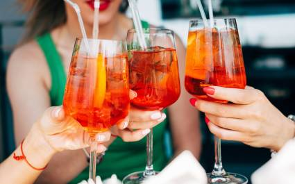 Enchanting Travels Italy Tours Woman hands toasting with aperol spritz cocktails