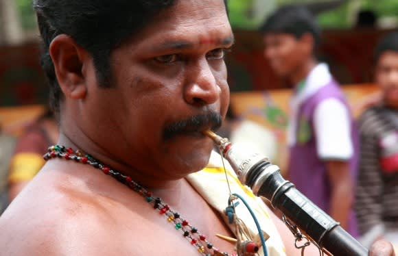 Ein Mann spielt Musik während des Onam Festes in Kerala, Indien