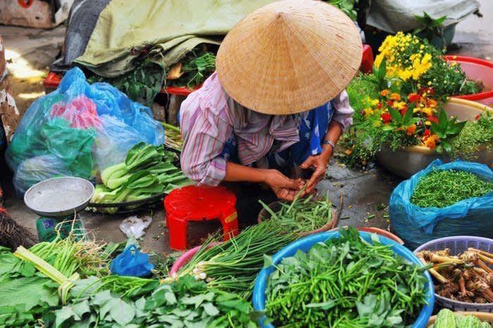 Vietnam Reisebericht - Eine vietnamesische Marktfrau verkauft frische Zutaten auf dem Markt