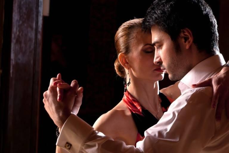 Festlich gekleidetes Paar in konzentrierter Pose tanzt den Tango