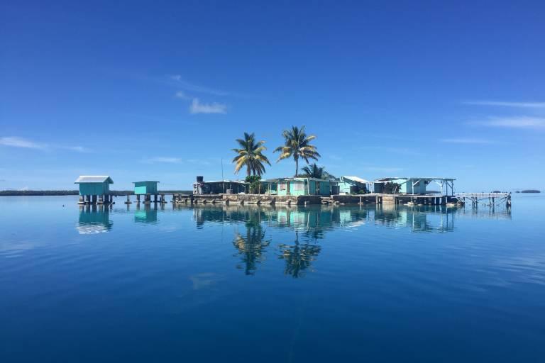 Hütten und Palmen im Wasser des Manihiki-Atolls der Cook-Inseln