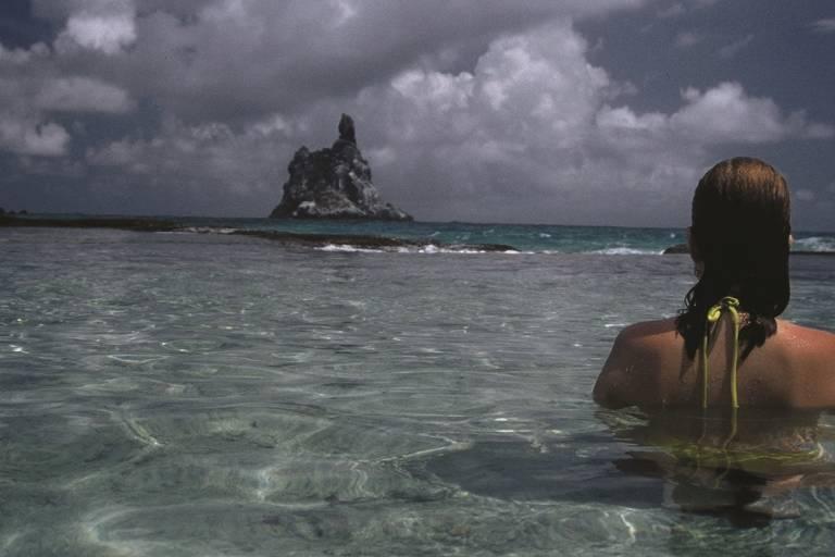 Frau badet in kristallklarem Wasser und blickt auf Felseninsel