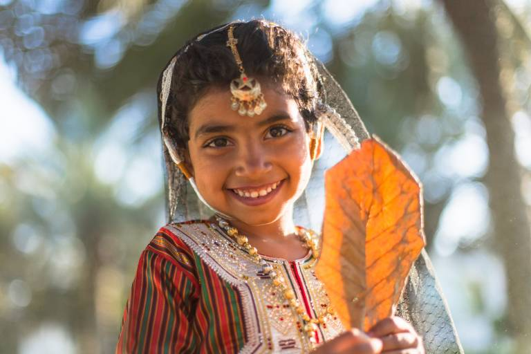Beautiful-Omani-girl-in-traditional-dress-is-playing-in-the-park-in-Oman