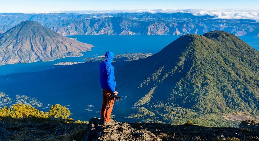 Guatemala travel guide - Enchanting TravelHiker with panorama view of Lake Atitlan and volcano San Pedro and Toliman early in the morning from peak of volcano Atitlan, Guatemala. Hiking and climbing on Vulcano Atitlan