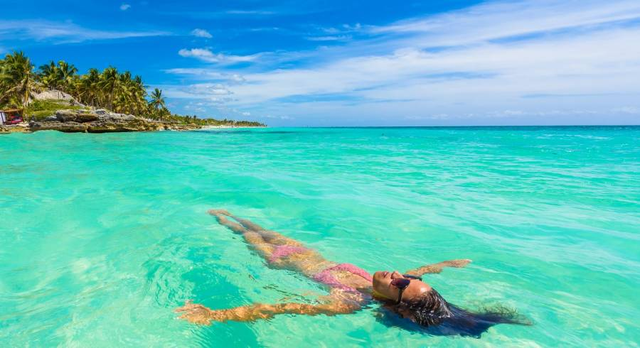 Enchanting Travels Mexico Tours relaxing in turquoise waters of Caribbean Sea in front of paradise beach in Tulum