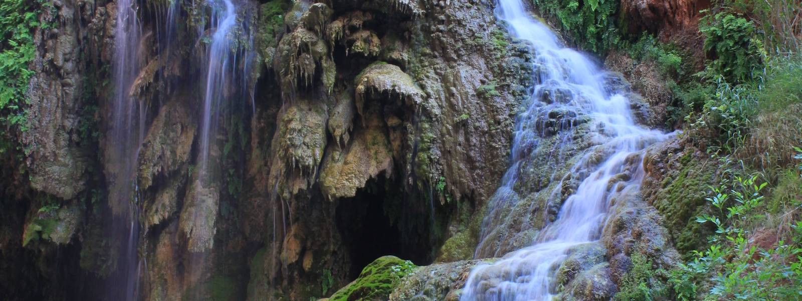 a large waterfall next to a rock