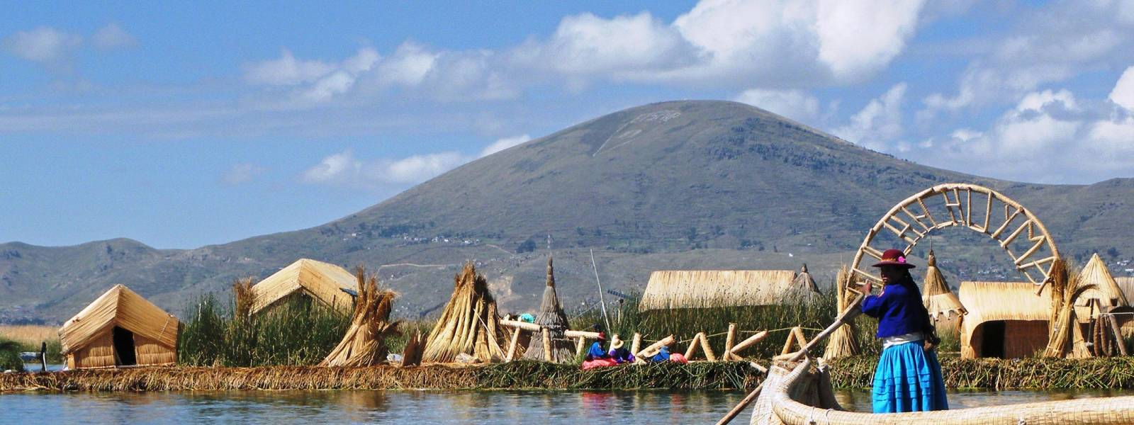 a small boat in a body of water with Lake Titicaca in the background