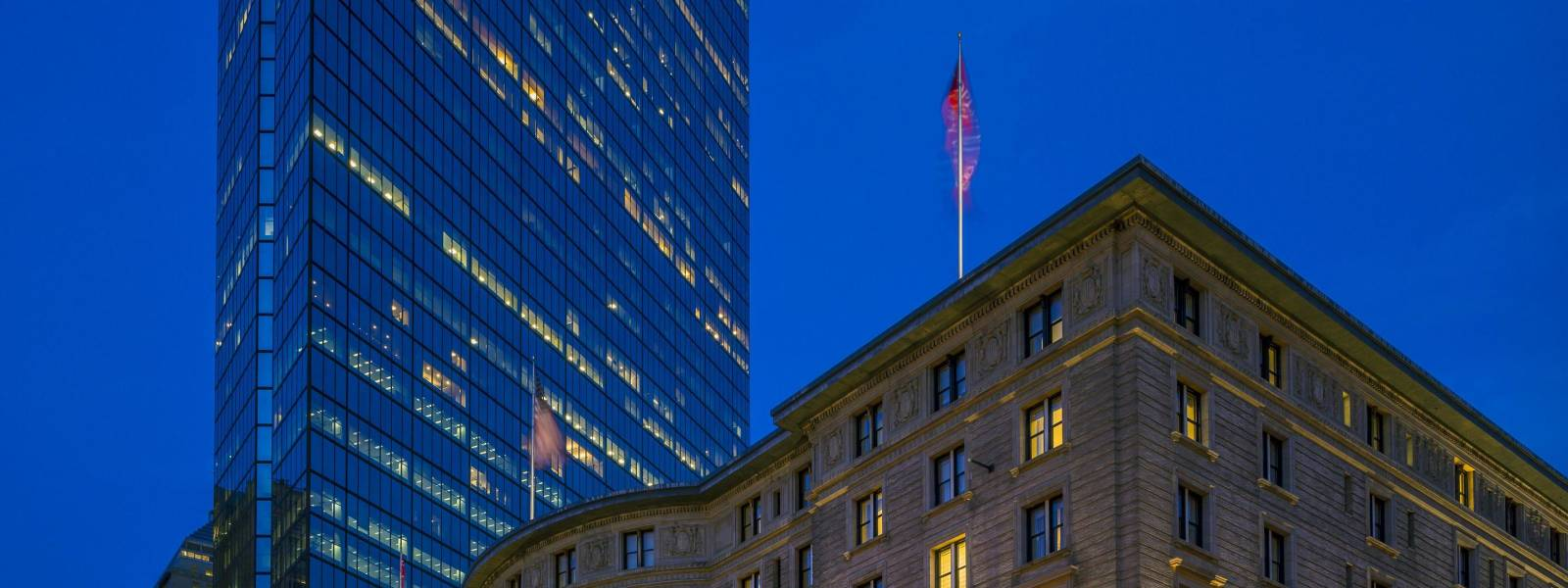 a lit up city at night with The Fairmont Copley Plaza Hotel in the background