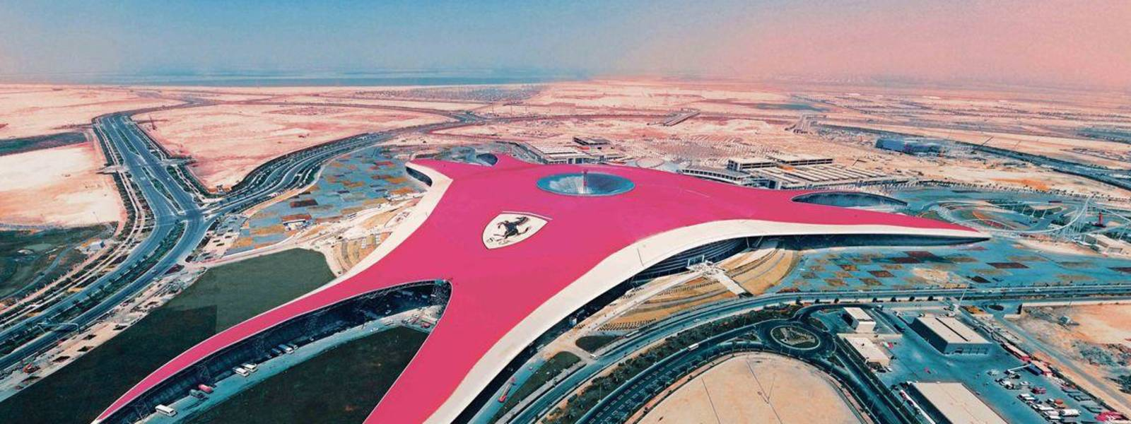 a train is parked on the beach with Ferrari World Abu Dhabi in the background