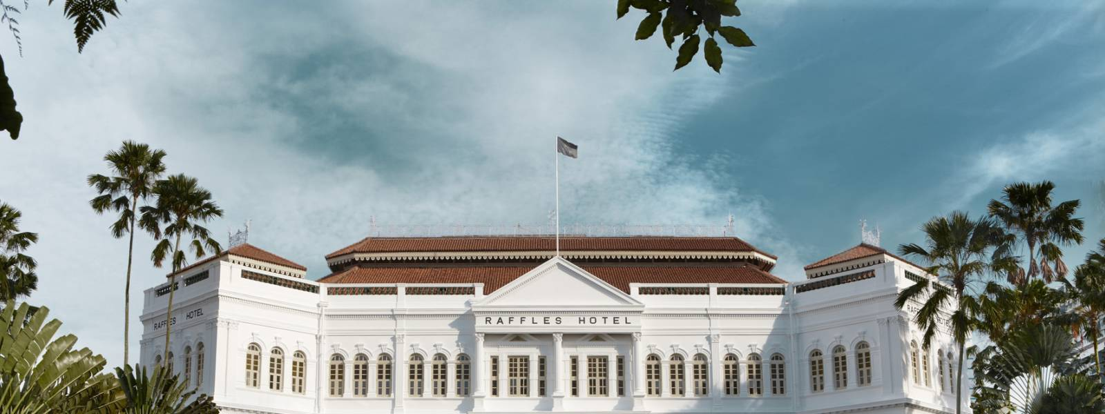 a large white building with trees in the background with Raffles Hotel in the background