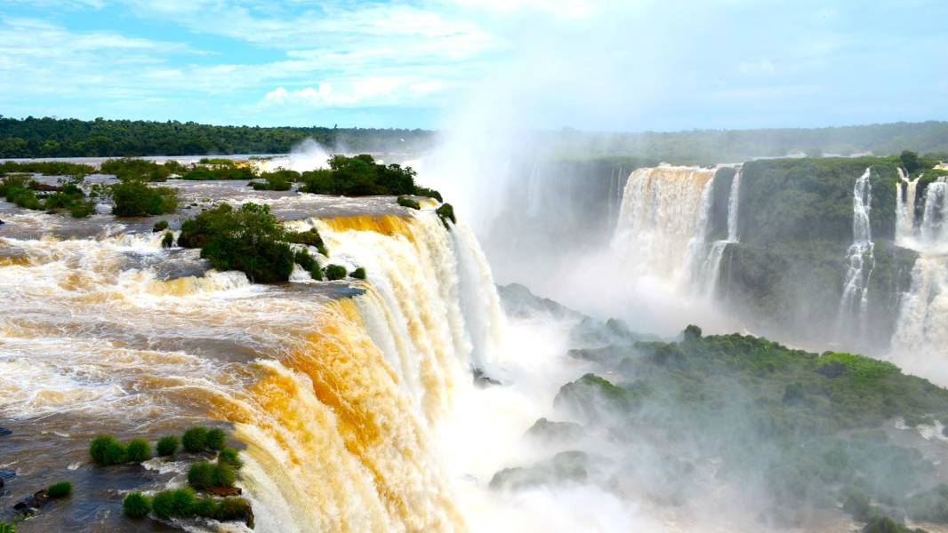 a large waterfall over some water with Iguazu Falls in the background