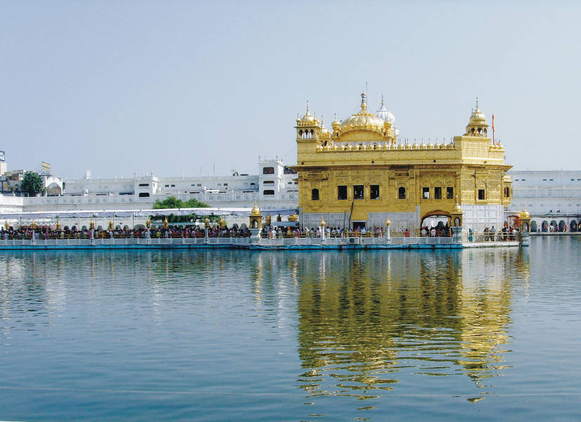 a large yellow boat in the water with Harmandir Sahib in the background