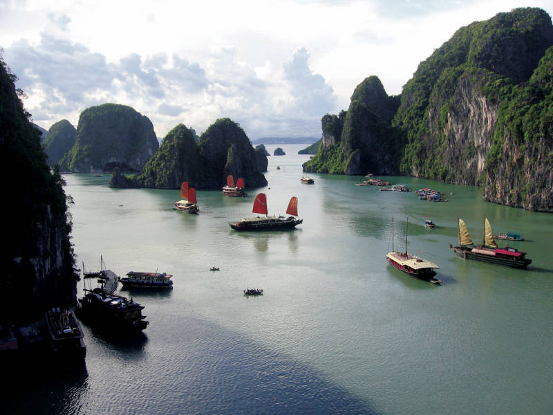 a group of people in a small boat in a body of water with Ha Long Bay in the background