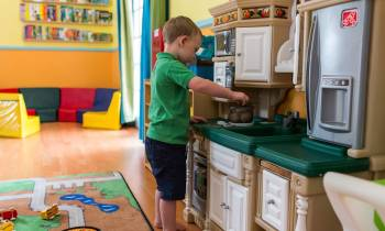 a little boy that is standing in the kitchen