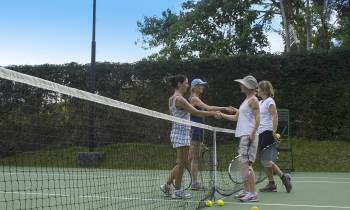 a group of people on a court with a racket
