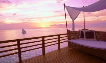 A sun lounger overlooks the sea, while the sun sets on a luxury holiday