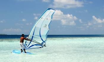 a man flying a kite in a boat on a body of water