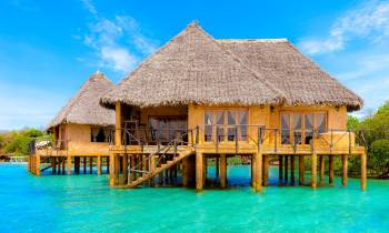 a large pool of water in front of a house with Bora Bora in the background