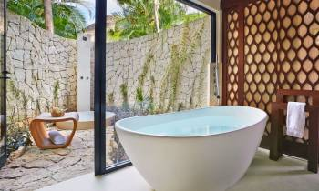 a large white tub sitting next to a stone wall