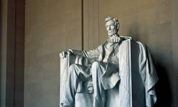 a statue of a person with Lincoln Memorial in the background