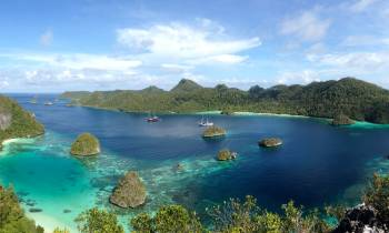 a small island in the middle of a body of water with Raja Ampat Islands in the background