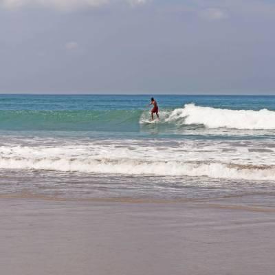 a man walking across a beach next to the ocean