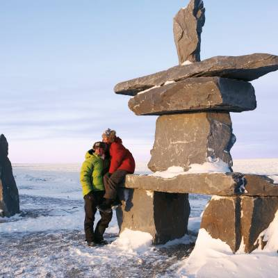 a group of people on a rock in the snow