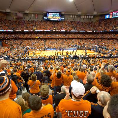 a large crowd of people with Carrier Dome in the background