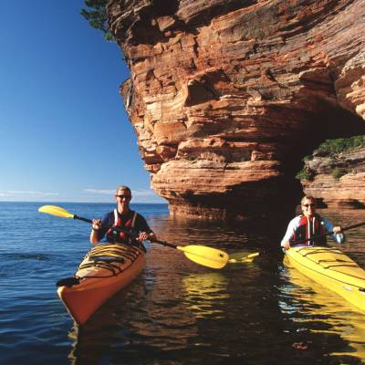 a group of people standing next to a body of water with Apostle Islands in the background