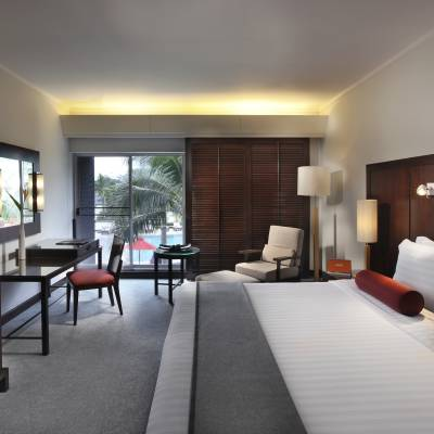 a bedroom with a bed and desk in a hotel room