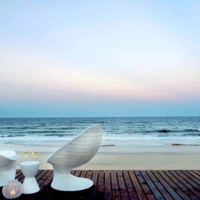 a chair sitting in front of a beach next to a body of water