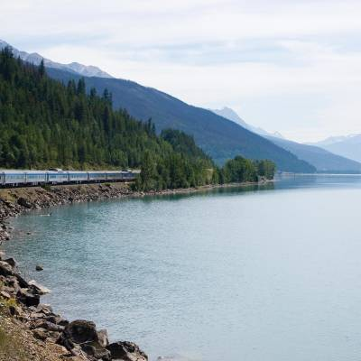 a train traveling down tracks next to a body of water